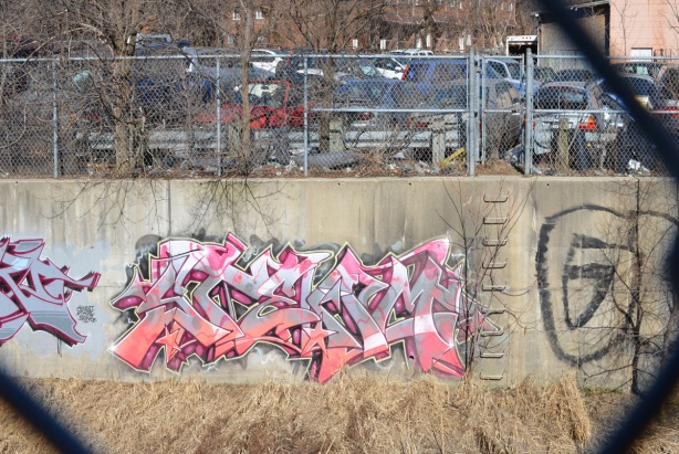 pink and white text graffiti on a canal wall