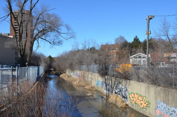 waterway with concrete sides, graffiti on the walls, some water,