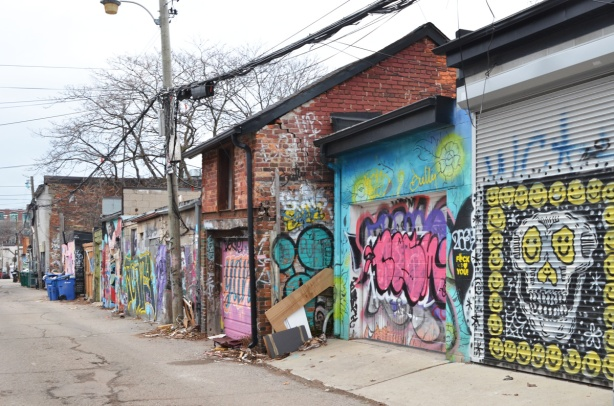 garages in a lane with graffiti and street art on them