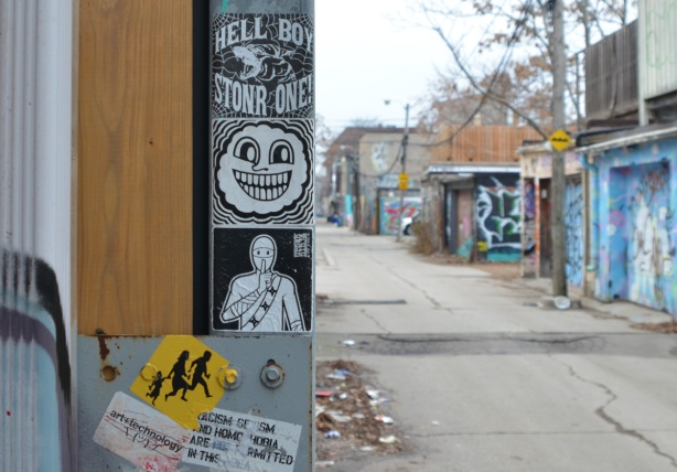 stickers on a pole with garages in the background, laneway,