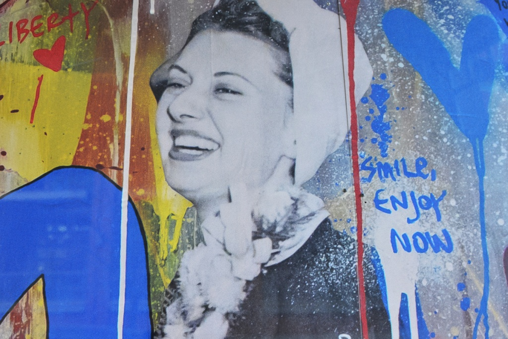 black and white picture of a woman in a white hat and white fluffy scarf on hoardings with blotches of yellow and blue, also blue writing that says smile enjoy now