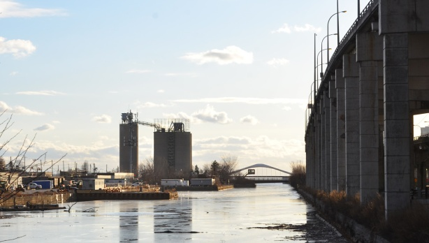 view from the Don Roadway back to the new Cherry Street bridge, looking west, with the Gardiner to the right, Keating channel with thin layer of ice on it, docks and a few buildings on the Port Lands side of the channel