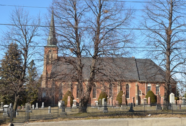 side of red brick church with cemetery between church and road, smell steeple, Knox United church