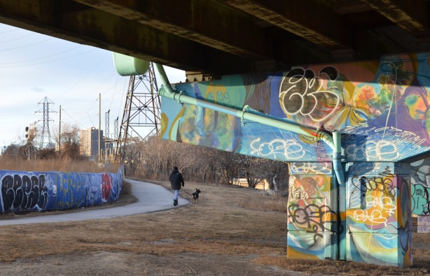 street art on the concrete bents holding up the ramp from D V P to Gardiner Expressway, walking path beside, with a man walking his dog,