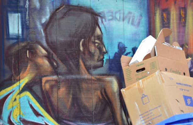 cardboard boxes stored against a wall with a mural of a woman from the back view