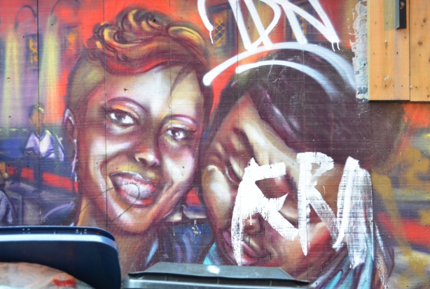 part of a mural, a couple, she has wavy hair pinned to the top of her head,