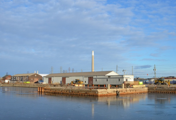 looking across the Keating Channel to a low rise building, square dock juts into the channel