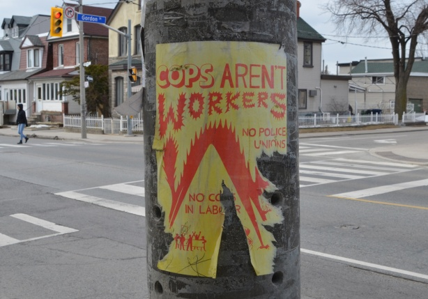 poster on a utility pole, yellow paper, orange words, Cops aren't workers,