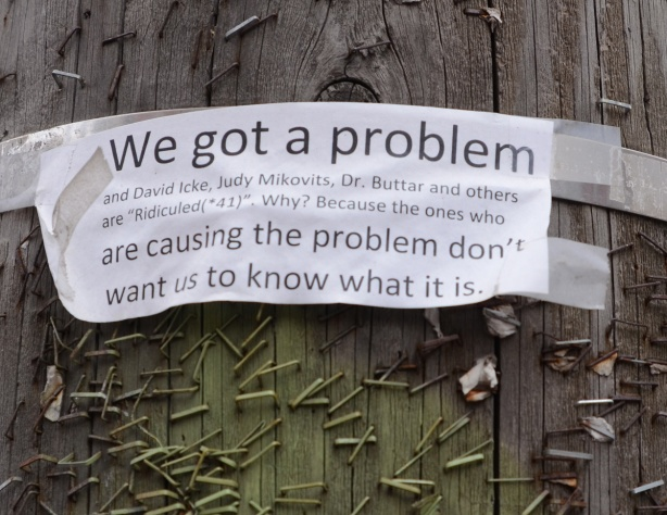 ripped paper on wooden pole with lots of staples, we got a problem, a covid protest piece