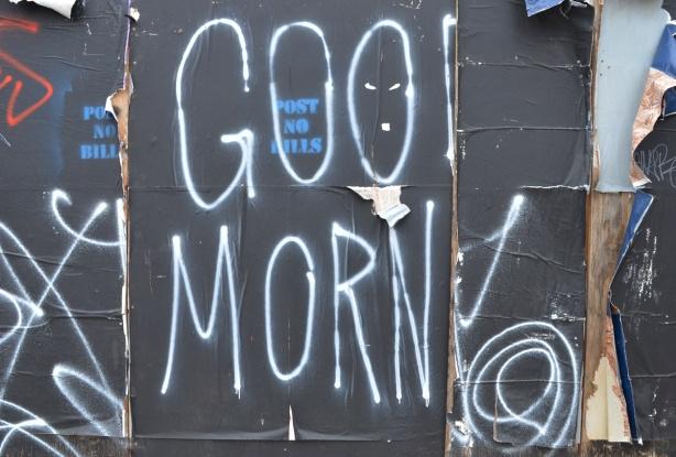 on black hoardings, large white letters that spell good morn