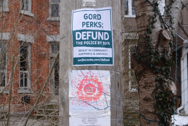 two posters on a pole, one is Gord PErks Defund the police by 50 percent and the other is Disco 3000