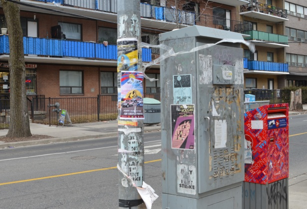 many posters on a pole and a metal box on a sidewalk
