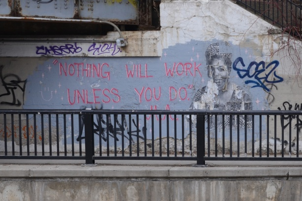 on an underpass wall, a black and white picture of a woman, Maya Angelou, and words in pink that say Nothing will work unless you do. This a quote from Maya Angelou