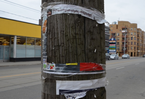 a poster on a wood utility pole has been torn but the four edges remain