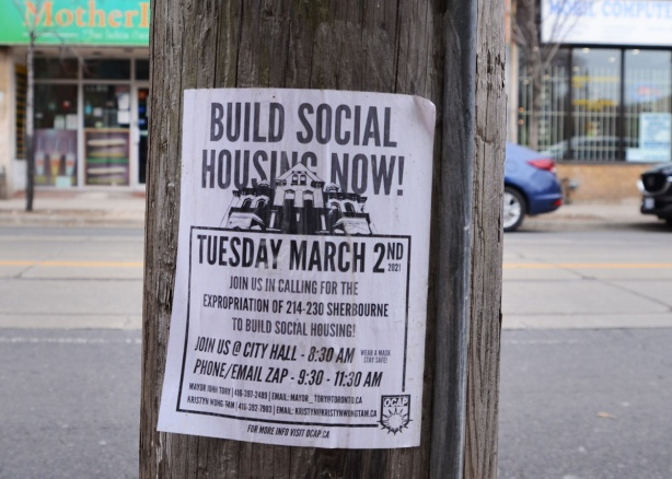 build social housing now poster on a pole, city hall protest, want to expropriate 214 to 230 Sherbourne Stret to build social housing