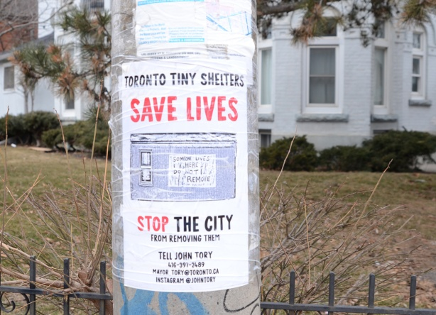a poster on a pole that wants Toronto city hall to save lives by not tearing down tiny shelters for the homeless that a man has been making