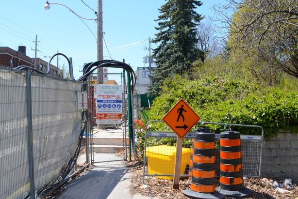 Pedestrian detour for crosstown subway and l r t construction, orange sign with arrow pointing right, leading pedestrians through the park