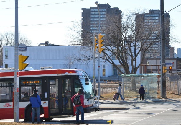 corner of Midland and Sheppard East, a Midland bus is northbound, bus shelter with 2 people across the street