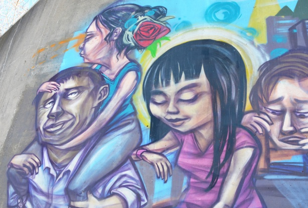 part of an elicser mural, a woman with a red rose in her hair sits on a man's shoulders, a woman in a pink dress is also in the picture
