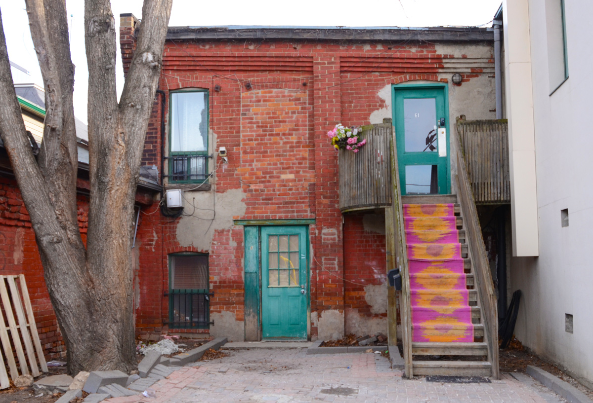 a bright pink and orange carpet on the stairs leading to the second storey behind an old brick building in Liberty Village