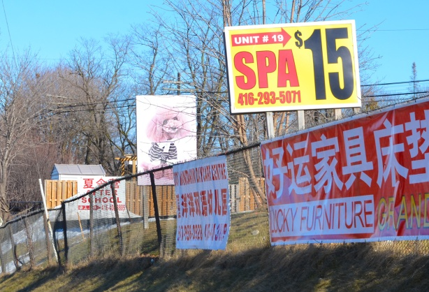 advertising signs along a fence, spa for 15 dollars, a Chinese furniture store, a pink poodle picture