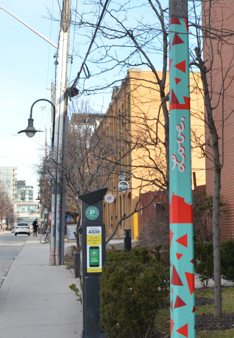 street in Liberty Village, one utility pole is painted in turquoise with red triangles and the word Love written in cursive