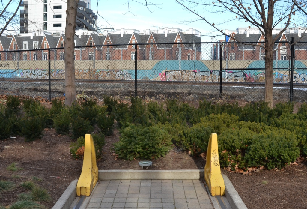 two yellow metal bumpers at the end of the railway tracks, left over from a real railway line, ends in park by a fence along another, real, train tracks, graffiti on the walls beyond the tracks, houses beyond that