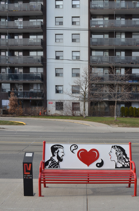 an apartment building across the street, a bench on the sidewalk in the foreground.  The bench is red with a picture on the back of a man and woman yelling at each other and a red heart in the middle