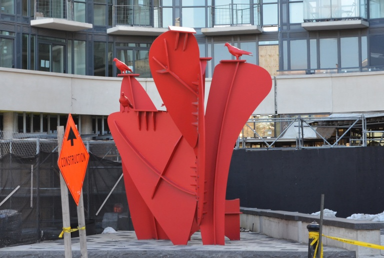 Red metal sculpture in front of a new condo development in Liberty Village, with red metal pigeons on top of the shapes