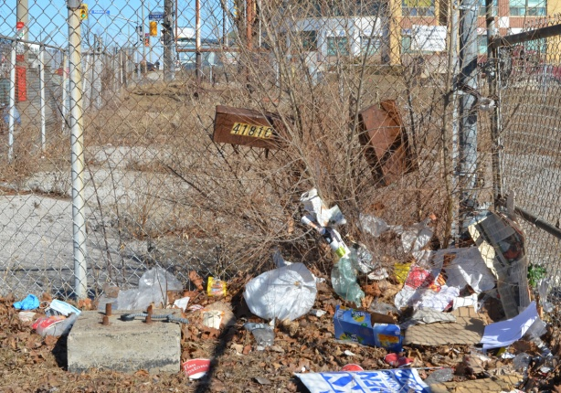 chainlink fence with rusty mailboxes, a lot of garbage has blown up against the fence