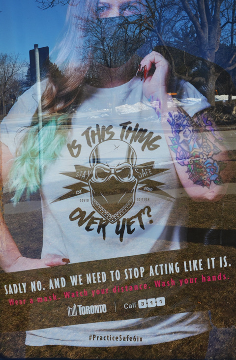 poster in a bus shelter, Covid-19, how it isn't over yet, practice safe six