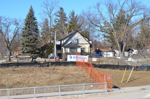side of a house, orange construction fence, ELlis Don sign, metal railling