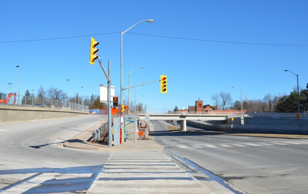sheppard avenue east just east of kennedy road, with GO train bridge overpass, all concrete, with access road to Go station on the left