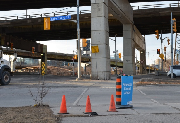 at the intersection of Don Roadway and Lakeshore Blvd, traffic cones and a blue sign that says sidewalk closed ahead