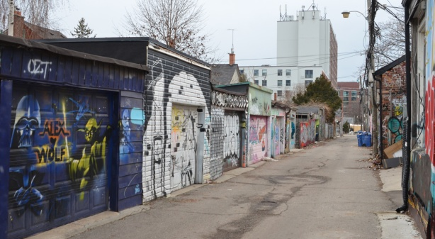 row of garages in an alley with graffiti and street art on them