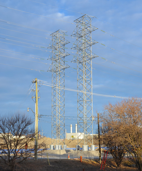 two tall metal hydro poles with lots of blue sky, power plant in the distance, and looking very small