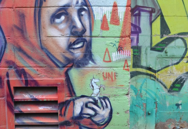 part of elicser mural of a man with a small beard in red hoodie, holding a small unicorn in his hand