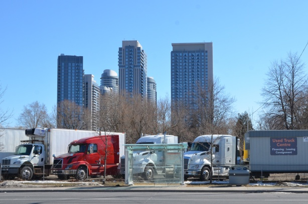 looking across the street to a used truck lot, tall condos in the background