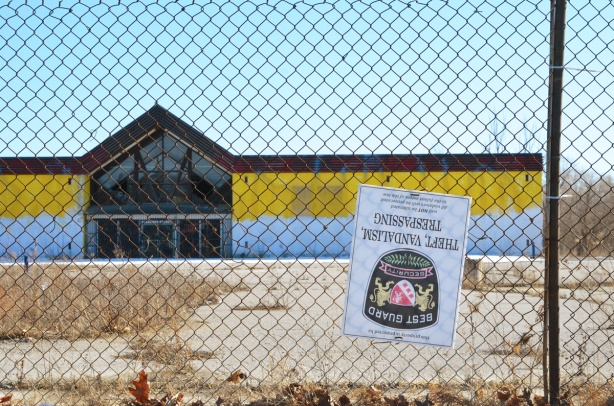 chainlink fence around an empty and abandoned store with yellow and white front, large vacant parking lot in front, a security sign is upside down on the fence