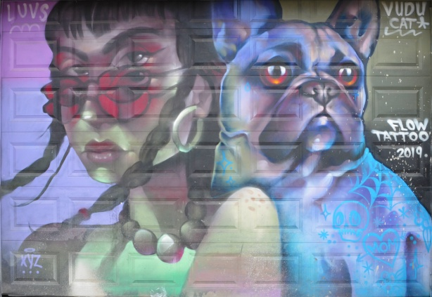 mural of a woman with large bead necklace and rose coloured sunglasses, beside of dog in shades of blue and purple,