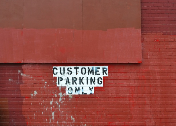 brick wall with a wood sign, all painted over in red, in the middle is black paint on white words that say customer parking only