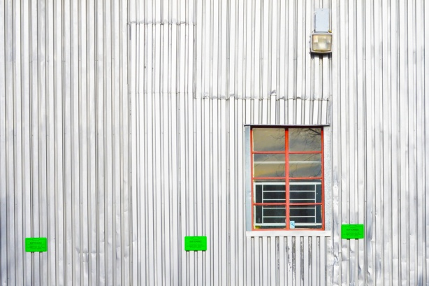 silver metal wall in vertical stripes, ridges, with a small window in the wall, with a small metal red bars