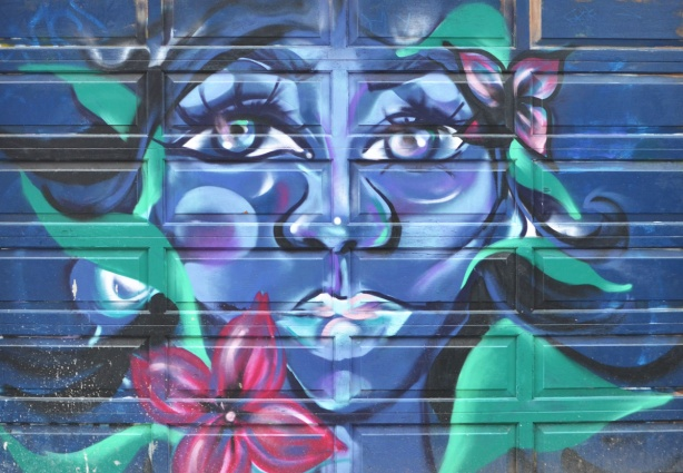 mural on a garage door, womans face in blue and purple