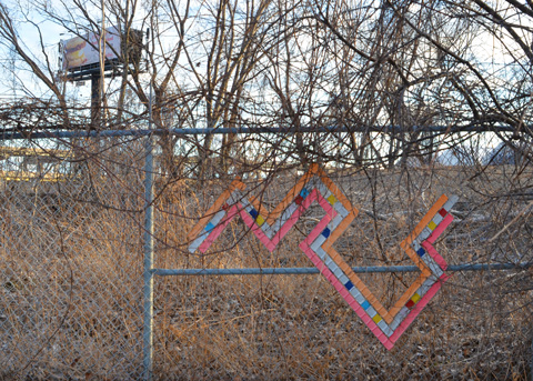 chain link fence with a design woven into it with different colours, artwork, shrubbery with no leaves (winter time), billboard on an expressway in the background