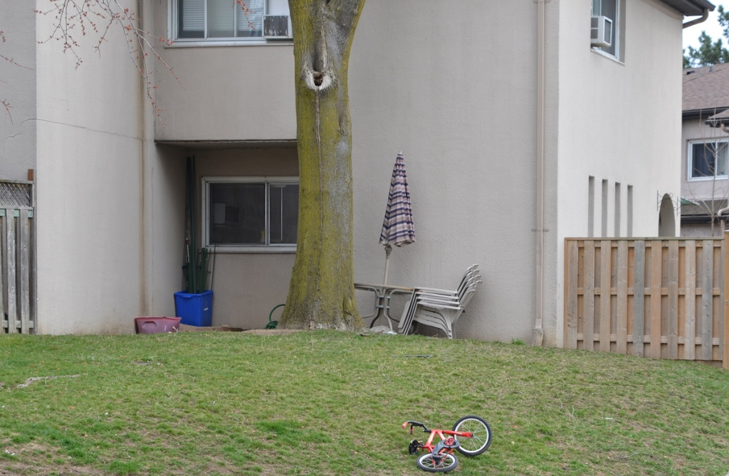 An orange kids bike lies on the grass outside a townhouse.  Patio chairs are stacked up by the house along with round table and folded umbrella