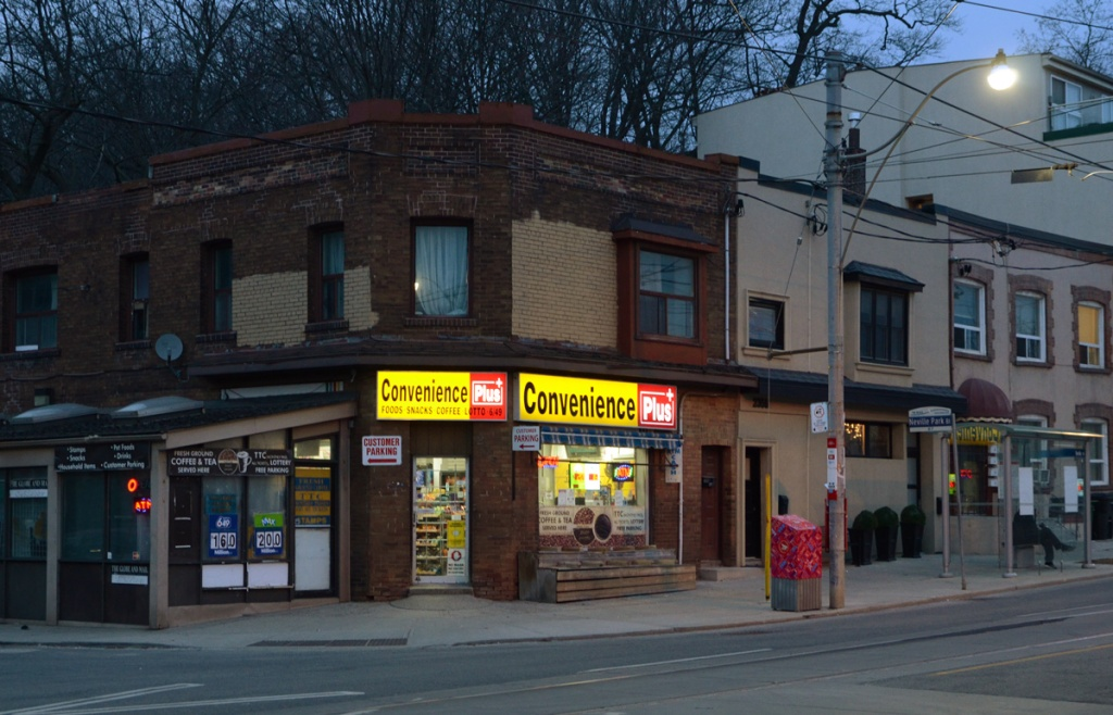 looking diagonally across the street at a corner store, Convenience Plus as it gets dark outside