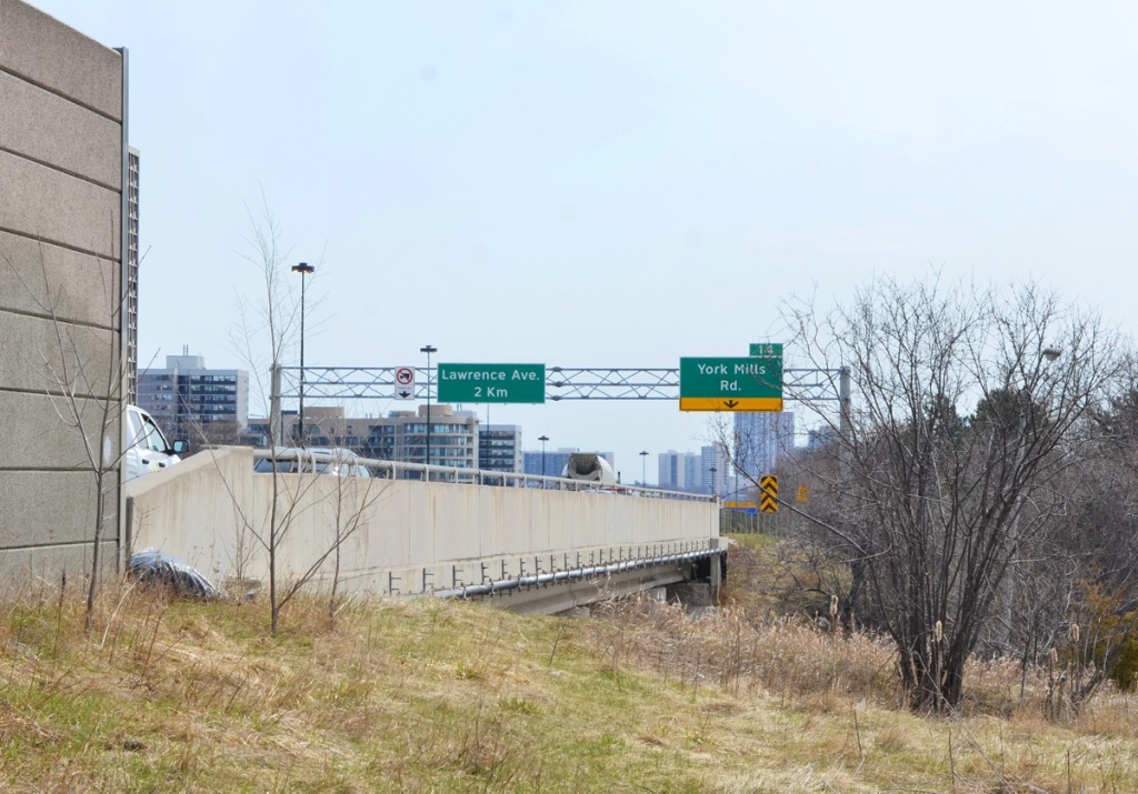 up on a hill, level with a DVP overpass over York Mills Road, concrete barrier at side of parkway, signs for exit ramp to York Mills, also sign saying Lawrence Ave in 2 km,