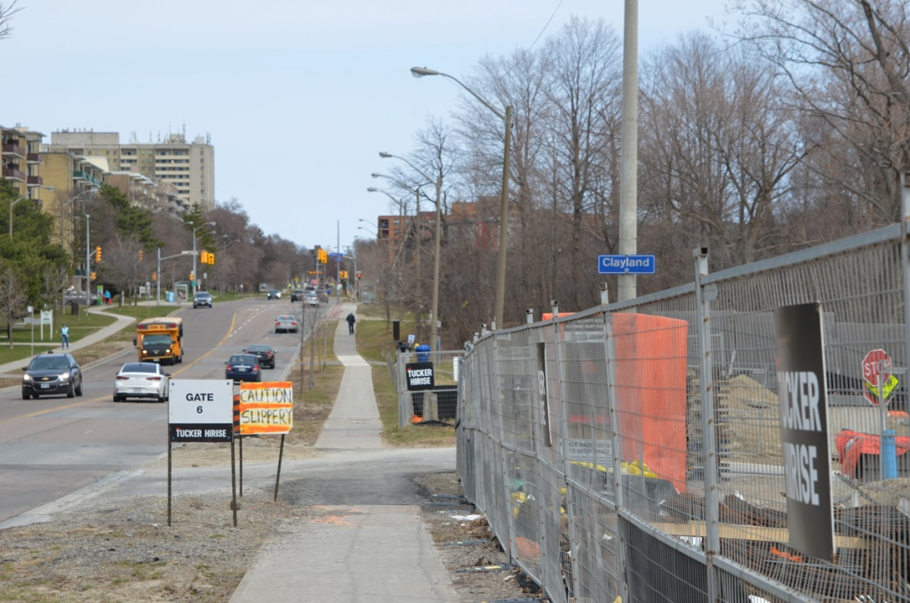 Looking east along York Mills Road, just east of the Don Valley Parkway, some condo construction on the right, traffic, school bus, low rise apartments on the left