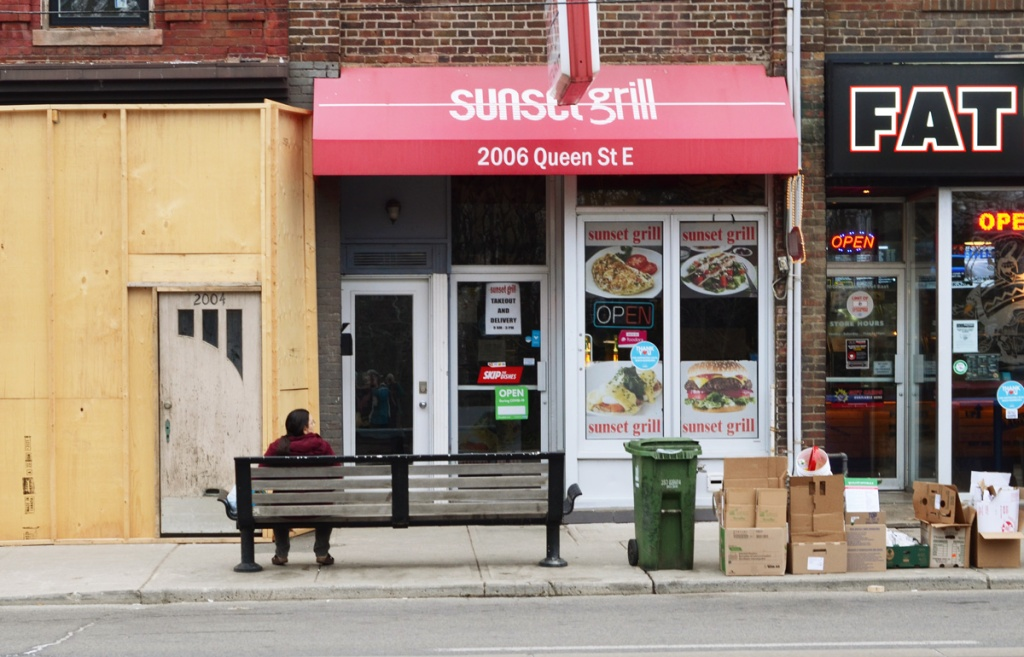 a person sits on a bench in front of the Sunrise Grill on Queen East