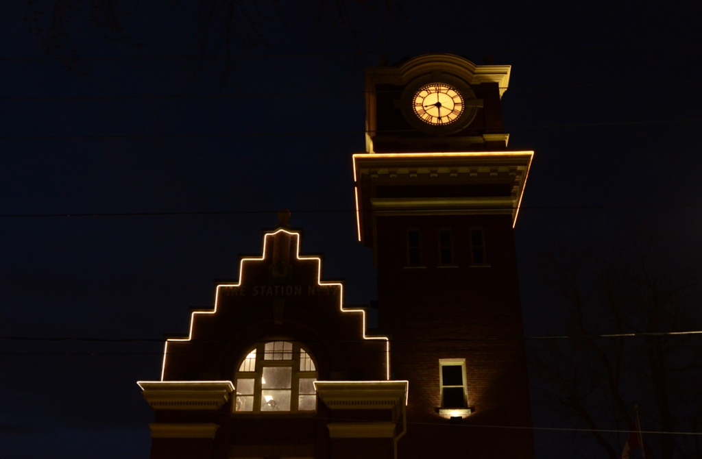 Evening lights, exterior of Firehall number 227 at Queen East and Woodbine, clock tower shows 8:20,